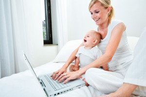 Woman with baby and laptop in bed